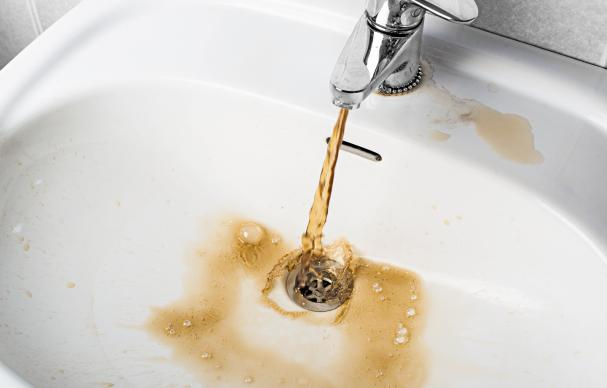 Domestic drinking water tap with rusty water from high metals concentration